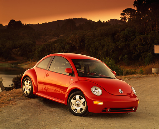 AUT 25 RK1097 07 © Kimball Stock 1999 VW Turbo New Beetle Red Front 3/4 View On Gravel Trees Background Filtered