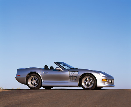 AUT 25 RK1107 03 © Kimball Stock 1999 Shelby Series 1 Convertible Silver Low 3/4 Front View On Pavement Hill Blue Sky