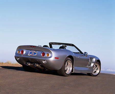 AUT 25 RK1108 01 © Kimball Stock 1999 Shelby Series 1 Convertible Silver 3/4 Rear View On Pavement Blue Sky