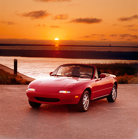 AUT 25 RK1115 01 © Kimball Stock 1990 Mazda Miata Convertible Red 3/4 Front View On Pavement By Water At Sunset