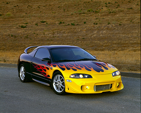 AUT 25 RK1166 05 © Kimball Stock 1999 Mitsubishi Eclipse GSX Custom Black With Flames 3/4 Front View On Pavement By Hill