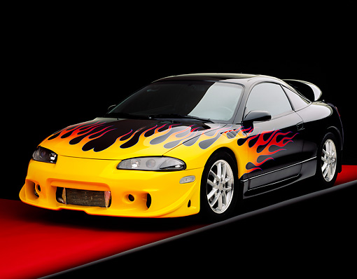 AUT 25 RK1169 09 © Kimball Stock 1999 Mitsubishi Eclipse GSX Custom Hot Rod Black With Flames 3/4 Front View On Red Floor Studio