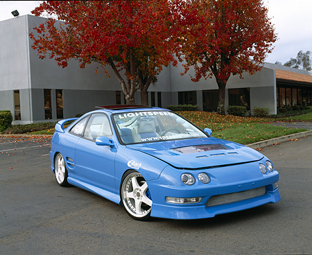 AUT 25 RK1193 02 © Kimball Stock 1998 Acura Integra Baby Blue Front 3/4 View On Pavement By Building