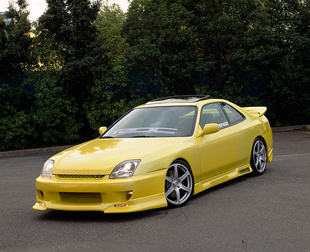 AUT 25 RK1209 04 © Kimball Stock 1999 Honda Prelude SH Yellow Front 3/4 View On Pavement By Trees