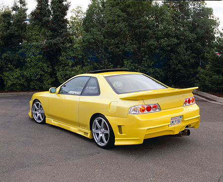 AUT 25 RK1210 01 © Kimball Stock 1999 Honda Prelude SH Yellow Rear 3/4 View On Pavement By Trees