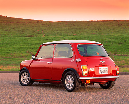 AUT 25 RK1223 04 © Kimball Stock 1998 Mini Cooper European Edition Red And White 3/4 Rear View On Pavement By Grass Hill Filtered