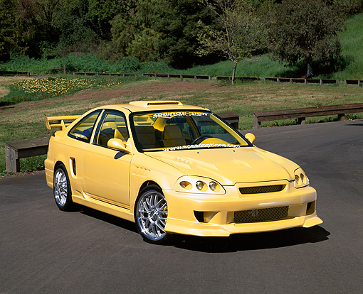 AUT 25 RK1228 02 © Kimball Stock 1998 Honda Civic Custom Yellow 3/4 Front View On Pavement By Grass And Trees