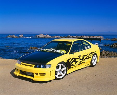 AUT 25 RK1238 01 © Kimball Stock 1994 Honda Accord LX Yellow Black Flames 3/4 Front View On Sand By Ocean