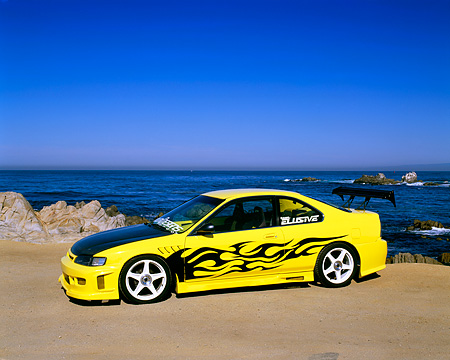 AUT 25 RK1239 01 © Kimball Stock 1994 Honda Accord LX Yellow Black Flames 3/4 Side View On Sand By Ocean