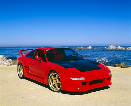 AUT 25 RK1243 02 © Kimball Stock 1991 Toyota MR2 Red Black With Black Hood 3/4 Front View On Sand By Ocean