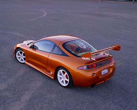 AUT 25 RK1293 05 © Kimball Stock 1997 Mitsubishi Eclispe Custom Orange 3/4 Rear View On Pavement