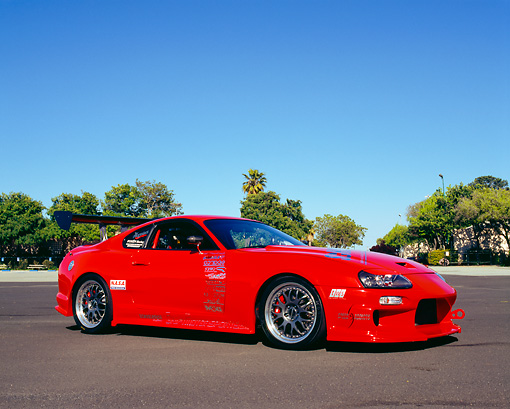 AUT 25 RK1348 03 © Kimball Stock 1994 Toyota Supra Red Custom Low 3/4 Side View On Pavement Trees Blue Sky