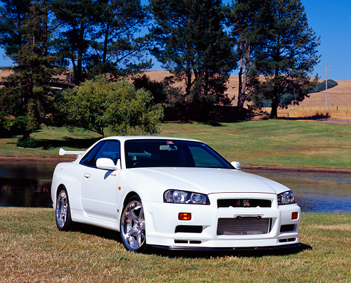 AUT 25 RK1354 04 © Kimball Stock 1999 Nissan Skyline GTR R34 White 3/4 Front View On Grass By Water And Trees