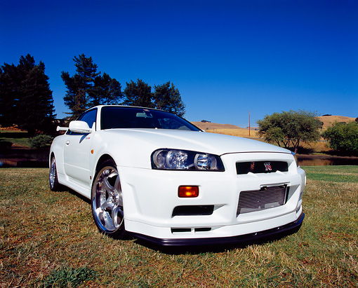 AUT 25 RK1355 04 © Kimball Stock 1999 Nissan Skyline GTR R34 White Wide Angle 3/4 Front View On Grass