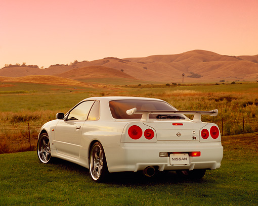 AUT 25 RK1370 03 © Kimball Stock 1999 Nissan Skyline GTR R34 White 3/4 Rear View On Grass Hills Filtered