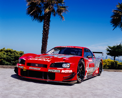 AUT 25 RK1373 03 © Kimball Stock 1999 Nissan Skyline Nismo Race Car Red Low 3/4 Front View By Palm Trees