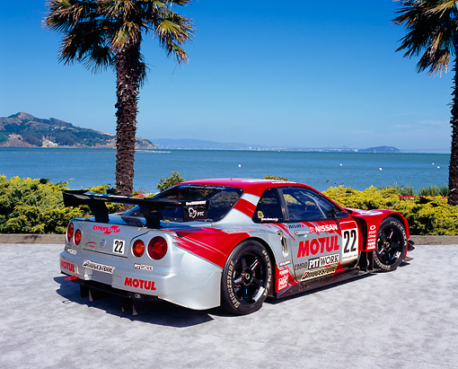 AUT 25 RK1378 03 © Kimball Stock 1999 Nissan Skyline Nismo Race Car Red 3/4 Rear View By Water And Palm Trees