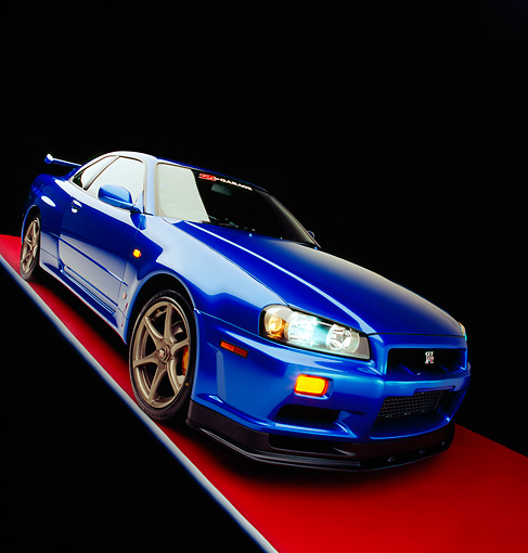AUT 25 RK1391 06 © Kimball Stock 1999 Nissan Skyline GTR Blue Slanted 3/4 Front View On Red Floor Gray Line Studio