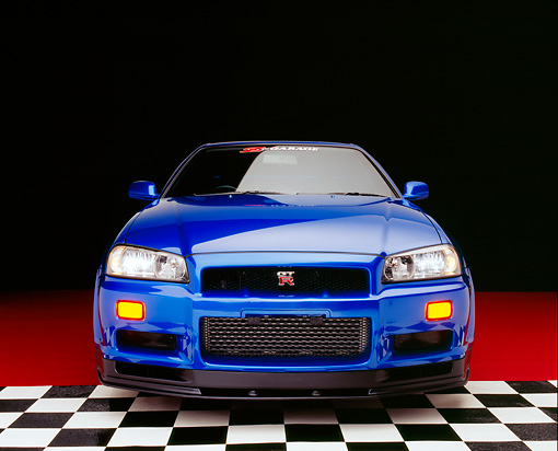 AUT 25 RK1395 01 © Kimball Stock 1999 Nissan Skyline GTR Blue Head On Shot On Checkered And Red Floor Studio