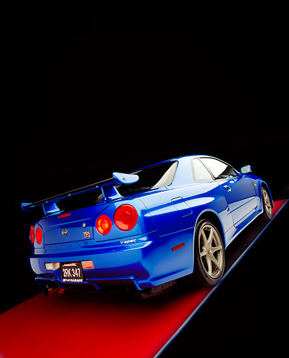 AUT 25 RK1396 02 © Kimball Stock 1999 Nissan Skyline GTR Blue Slanted 3/4 Rear View On Red Floor Gray Line Studio