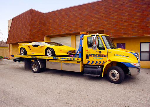 AUT 25 RK1407 01 © Kimball Stock 1992 Vector W-8 Twin Turbo Yellow On Tow Truck By Building
