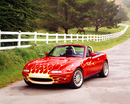 AUT 25 RK1408 01 © Kimball Stock 1990 Mazda Miata Convertible Red With Flames Front 3/4 View On Pavement By White Fence