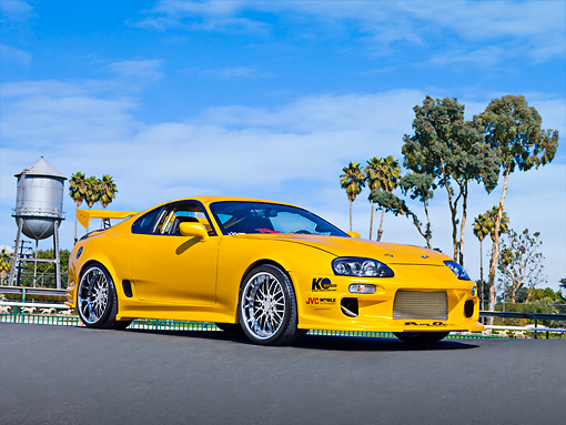 AUT 25 RK1431 01 © Kimball Stock 1998 Toyota Supra Custom Yellow 3/4 Front View On Pavement By Trees Blue Sky