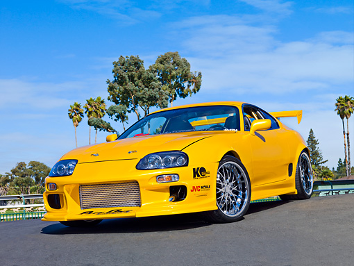 AUT 25 RK1435 01 © Kimball Stock 1998 Toyota Supra Custom Yellow 3/4 Front View On Pavement Blue Sky