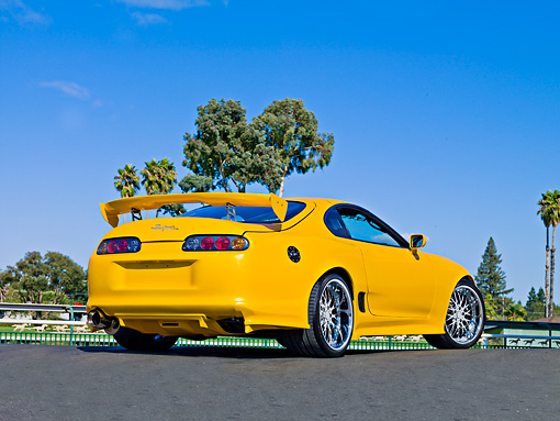 AUT 25 RK1436 01 © Kimball Stock 1998 Toyota Supra Custom Yellow 3/4 Rear View On Pavement Blue Sky