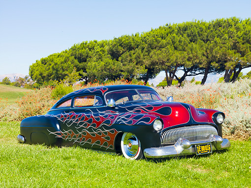 AUT 26 BK0001 01 © Kimball Stock 1951 Chevrolet Fleetline Hot Rod Black With Red Flames 3/4 Front View On Grass By Trees