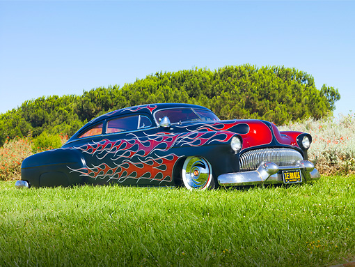 AUT 26 BK0002 01 © Kimball Stock 1951 Chevrolet Fleetline Hot Rod Black With Red Flames 3/4 Front View On Grass By Trees