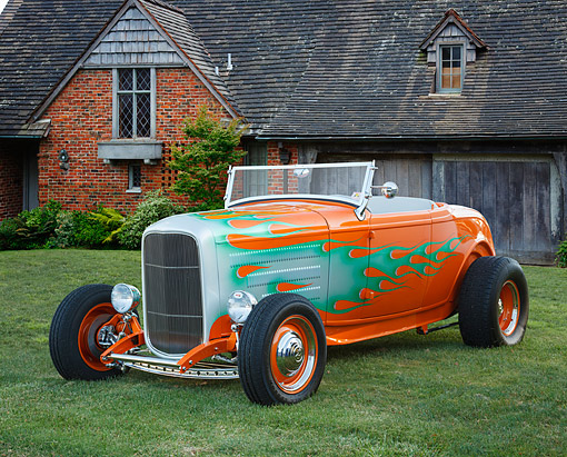 AUT 26 BK0018 01 © Kimball Stock 1932 Ford Roadster Sunset Pearl With Green Flames 3/4 Front View On Grass By Brick House