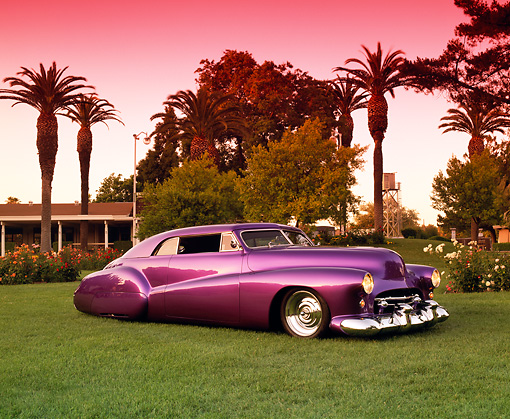 AUT 26 RK0250 01 © Kimball Stock 1947 Buick Full Custom Convertible Purple Low 3/4 Side View On Grass By Trees And Flowers Red Sky