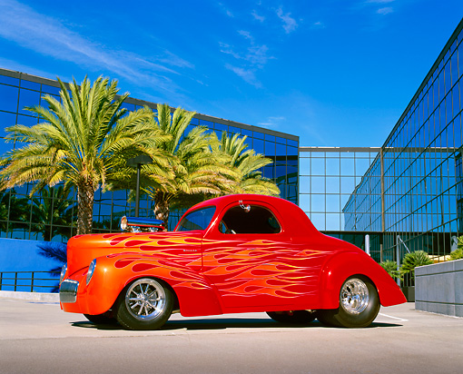 AUT 26 RK0329 06 © Kimball Stock 1941 Willys Prostreet Coupe Red With Flames 3/4 Side View On Pavement By Glass Building
