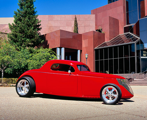 AUT 26 RK0414 03 © Kimball Stock 1937 Ford Coupe Red 3/4 Front View On Pavement By Museum And Trees