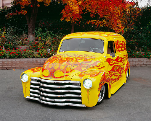 AUT 26 RK0501 03 © Kimball Stock 1950 Chevy Panel Yellow With Flames 3/4 Front View On Pavement By Fall Trees