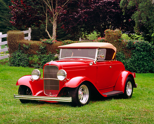 AUT 26 RK0560 03 © Kimball Stock 1932 Ford Roadster Red 3/4 Front View On Grass By Bushes