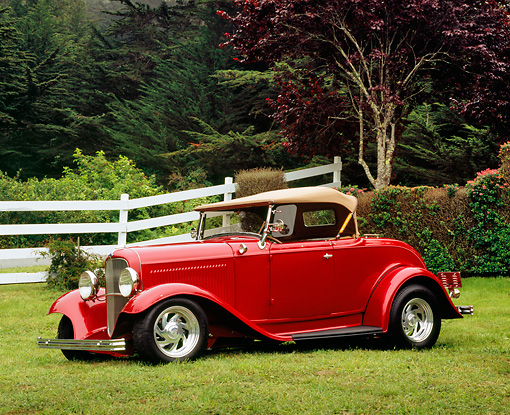 AUT 26 RK0561 02 © Kimball Stock 1932 Ford Roadster Red 3/4 Front View On Grass By White Fence And Trees