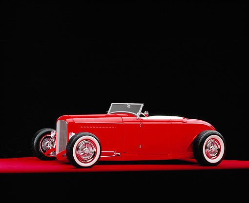 AUT 26 RK0564 08 © Kimball Stock 1932 Ford Channel Roadster Red 3/4 Side View On Red Floor Studio