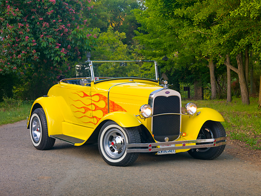 AUT 26 RK2794 01 © Kimball Stock 1931 Ford Roadster Hot Rod Yellow With Flames 3/4 Front View On Pavement By Trees