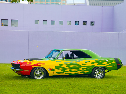 AUT 26 RK2807 01 © Kimball Stock 1970 Dodge Dart Swinger Hot Rod Red, Yellow, Green Profile View On Grass By Building