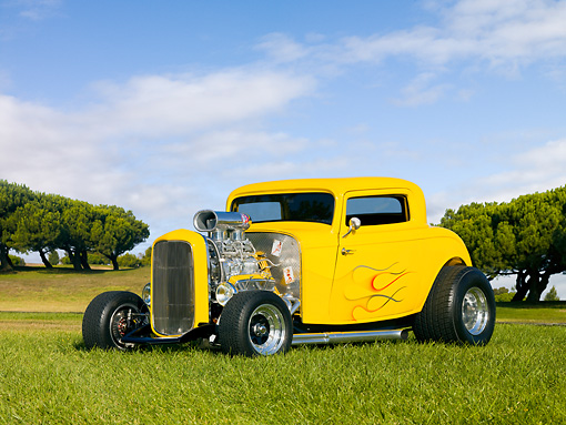 AUT 26 RK2891 01 © Kimball Stock 1932 Ford 3 Window Coupe Hot Rod Yellow With Flames 3/4 Front View On Grass
