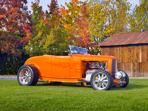AUT 26 RK2915 01 © Kimball Stock 1932 Ford Hi-Boy Roadster Hot Rod Orange 3/4 Front View On Grass By Barn