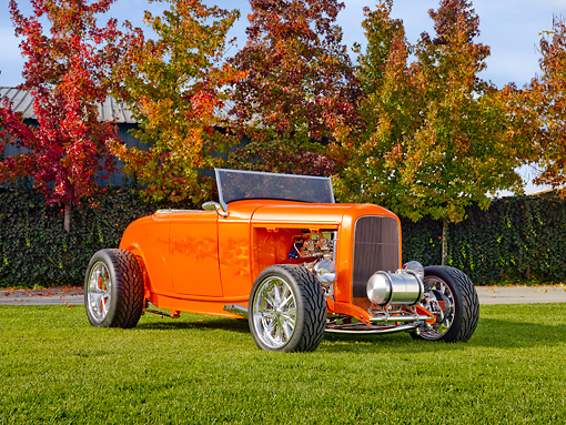 AUT 26 RK2916 01 © Kimball Stock 1932 Ford Hi-Boy Roadster Hot Rod Orange 3/4 Front View On Grass By Trees