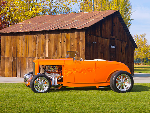 AUT 26 RK2917 01 © Kimball Stock 1932 Ford Hi-Boy Roadster Hot Rod Orange Profile View On Grass By Barn