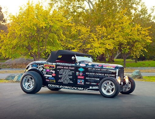AUT 26 RK2921 01 © Kimball Stock 1932 Ford Roadster Hot Rod Black With Decals 3/4 Front View On Pavement By Trees