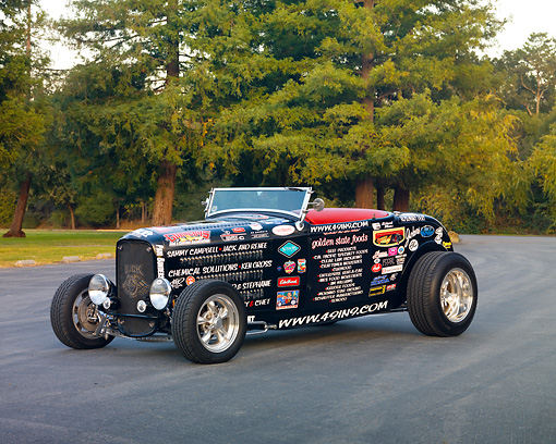 AUT 26 RK2922 01 © Kimball Stock 1932 Ford Roadster Hot Rod Black With Decals 3/4 Front View On Pavement By Trees