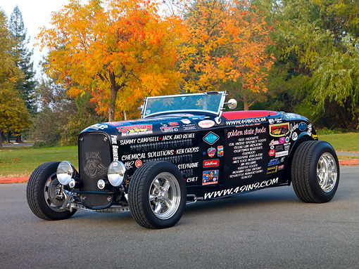 AUT 26 RK2923 01 © Kimball Stock 1932 Ford Roadster Hot Rod Black With Decals 3/4 Front View On Pavement By Trees