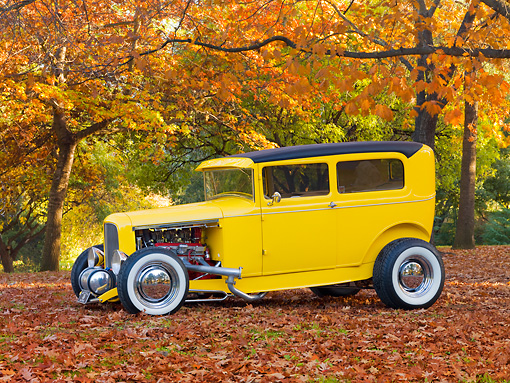 AUT 26 RK2937 01 © Kimball Stock 1931 Ford Sedan Hot Rod Yellow 3/4 Front View On Fallen Leaves By Trees