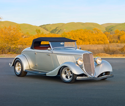 AUT 26 RK2957 01 © Kimball Stock 1933 Ford Roadster Hot Rod Silver 3/4 Front View On Pavement By Hills